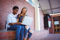 Schoolgirls sitting against brick wall and using laptop Royalty Free Stock Photos