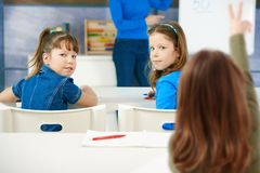 Schoolgirls sitting at desk in classroom. Schoolgirls learning in primary school classroom, looking back to camera. Elementary age children Stock Images
