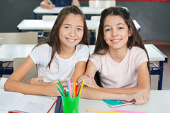 Schoolgirls Sitting At Desk In Classroom Stock Photo