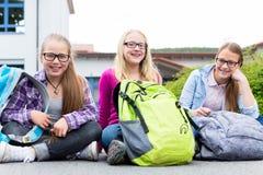 Schoolgirls sitting in schoolyard at school Royalty Free Stock Photo