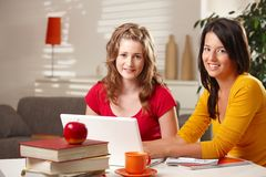 Schoolgirls smiling at table. Royalty Free Stock Image