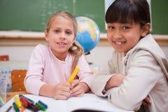 Schoolgirls som tecknar, medan se kameran Arkivfoton