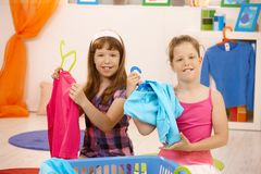 Schoolgirls sorting clothes at home Stock Photo