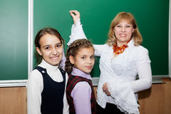 Schoolgirls and teacher at the blackboard royalty free stock images