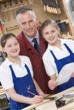 Schoolgirls and teacher in woodwork class Stock Photography