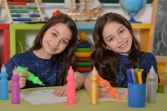 Schoolgirls twins on lesson of art Stock Image