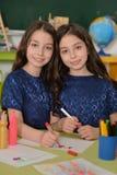 Schoolgirls twins on lesson of art Royalty Free Stock Photo