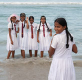 Schoolgirls in uniform playing on the beach Royalty Free Stock Photos