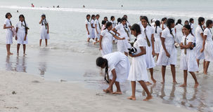 Schoolgirls in uniform playing at the beach Stock Image