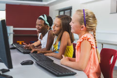 Schoolgirls using computer in classroom Royalty Free Stock Photography