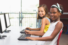 Schoolgirls using computer in classroom Royalty Free Stock Image