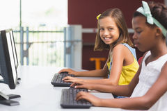 Schoolgirls using computer in classroom Royalty Free Stock Photo