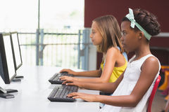 Schoolgirls using computer in classroom Stock Photo