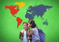 Schoolgirls whispering in front of colorful world map stock photo