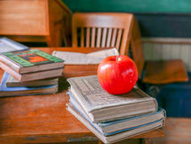Schoolhouse Apple. Old time schoolhouse with red apple on teacher`s desk with books and chalkboard Stock Image