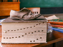 Schoolhouse Dictionary. Old time school house with very large dictionary and old leather shoe atop with schoolbooks, chalkboard, desk and chair Stock Photography