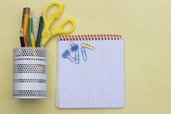 Schoolhulpmiddelen zoals gele schaar, potlood, heerser, gom, en potloodgeval, over een gele flatlay, hoogste mening stock afbeelding