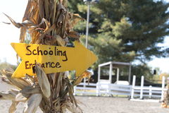 Schooling Entrance. Bright yellow sign nestled into a cornstalk and pointing the way to the entrance of an equestrian ring.  Judges stand noted in the background Stock Image