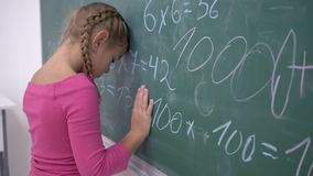 Schooling, female pupil tired of studies standing near blackboard with mathematics examples stock video