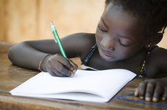 Schooling Symbol - African Young Girl Writing Notes Real People. Back To School Symbol - African Girl Toothy Huge Smile Showing Red Pencil. Little African girl Stock Photo