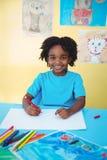 Schooljong geitje die op een blad trekken Stock Foto