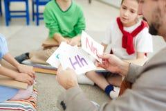 Schooljonge geitjes die alfabet leren stock afbeeldingen
