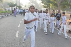 Schooljonge geitjes die bij Hyderabad 10K Looppasgebeurtenis lopen, India Stock Afbeelding