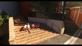 Schooljonge geitjes die bij schooltrap zitten stock video