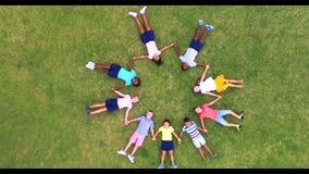 Schooljonge geitjes die handen houden terwijl het liggen in cirkel op gras stock videobeelden
