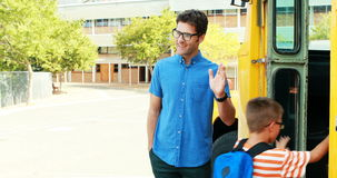 Schooljonge geitjes die hoogte vijf geven aan leraar terwijl het ingaan van de bus stock videobeelden