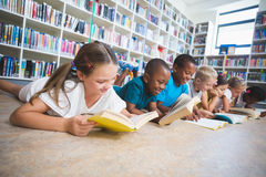 Schooljonge geitjes die op het boek van de vloerlezing in bibliotheek liggen stock afbeelding