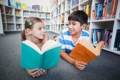 Schooljonge geitjes die op vloer liggen en een boek lezen in bibliotheek stock foto's