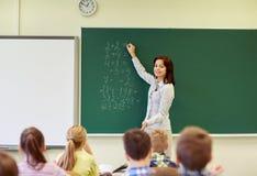 Schooljonge geitjes en leraar die op bord schrijven Stock Fotografie