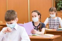 Schooljonge geitjes met beschermingsmasker tegen griepvirus bij les stock fotografie