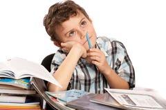 Schooljongen aarzelend aan het doen van thuiswerk stock fotografie
