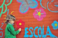Schooljongen bij de muur Stock Fotografie