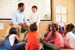 Schooljongen bij voorzijde van elementaire klasse met leraar stock afbeelding