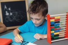 Schooljongen die aan wiskundethuiswerk werken Stock Foto