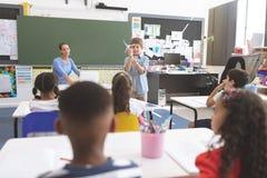 Schooljongen die aan zijn klasgenoten over windmolen in klaslokaal verklaren stock foto