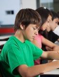 Schooljongen die bij Bureau met binnen Klasgenoten bestuderen stock foto's