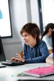 Schooljongen die Desktoppc in Computerlaboratorium met behulp van stock foto