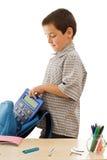 Schooljongen die een calculator in de schooltas zet Stock Afbeelding