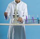 Schooljongen die een microscoop met chemische producten in reageerbuizen gebruiken stock fotografie