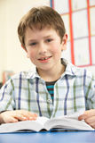 Schooljongen die Handboek in Klaslokaal bestudeert Royalty-vrije Stock Afbeeldingen