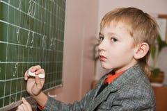 Schooljongen die jn de raad schrijft stock foto's