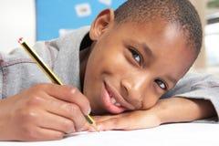 Schooljongen die in Klaslokaal bestudeert Stock Foto's