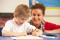 Schooljongen die in Klaslokaal met Leraar bestudeert Stock Foto