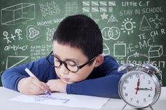 Schooljongen die met een klok op de lijst bestuderen Stock Afbeelding