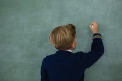 Schooljongen die met krijt op bord schrijven Stock Afbeeldingen