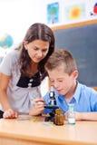 Schooljongen die microscoop onderzoeken Royalty-vrije Stock Afbeeldingen